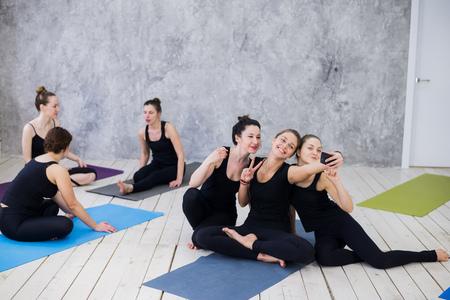 Drie jonge vrouwen die selfie na training bij yogales Stockfoto