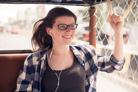 Traveling Asia. Young pretty girl enjoying trip in traditional thai bus Stock Photo