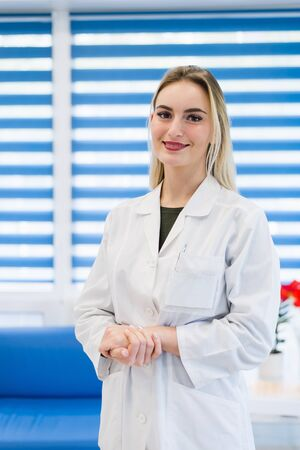 dentalcare: Portrait of a young female doctor wearing a white coat posing in hospital office