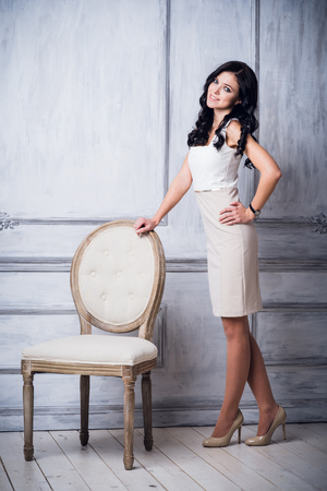 Fashion shot of young beautiful woman in white short dress standing near antique chair in front of luxury white wall with decorative mouldings Stock Photo