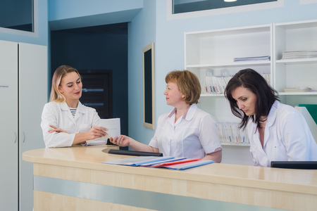 Doctors having discussion hospital reception while people sitting in background Stockfoto