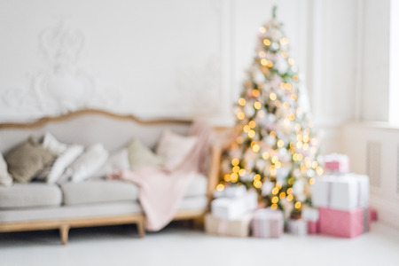 Blurred background. Luxury living room interior with sofa decorated chic Christmas tree, gifts, plaid and pillows