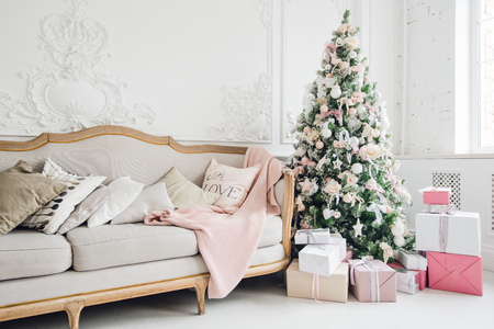 Christmas tree with a white sofa in a white room. 스톡 콘텐츠