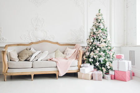 New Year's holiday or celebration, the mood, Stylish Christmas minimalistic interior, Presents and wrapped gifts under the Christmas tree. large white living room with a vintage sofa.