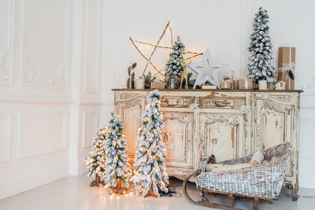 Christmas decoration on ancient vintage old commode chest of drawers. Hand made craft gifts, candels and a tree at background. Stock Photo