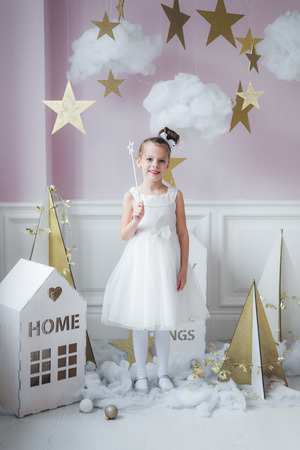 Little happy fairy or angel with magic wand on Holiday theme. Portrait of pretty caucasian little angel wearing white dress and holding magic stick 스톡 콘텐츠
