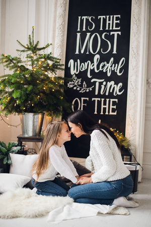 Close-up photo of little girl in knitted sweater kiss her mother while sitting on sofa at Christmas Stock Photo