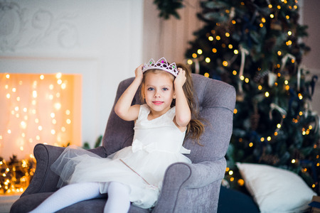 Cute little girl in smart white dress Christmas around the fireplace which decorated with holiday garland Stock Photo
