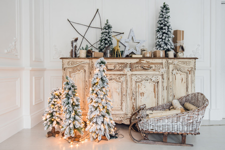 Christmas tree on wooden chest of drawers commode bureau in white interior, decorated with artificial flowers, garlands and toys