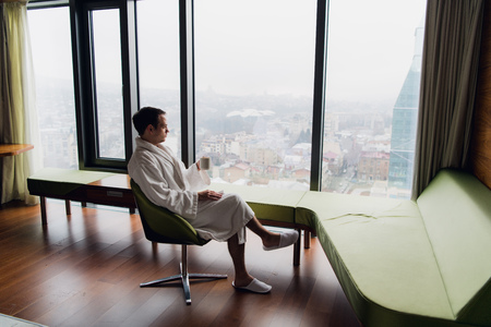 Young handsome carefree man wearing bathrobe near modern full length window enjoying a cup of coffee while looking outside, good morning. Horizontal photo banner for website header design with copy space for text