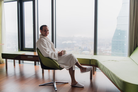Man in bathrobe drinking coffee, looking at cityscape Stock Photo