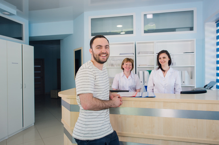 Male patient with doctor and nurse at reception desk in hospital Stockfoto