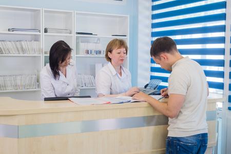 Männlicher Patient mit Doktor und Krankenschwester am Aufnahmeschreibtisch im Krankenhaus Standard-Bild