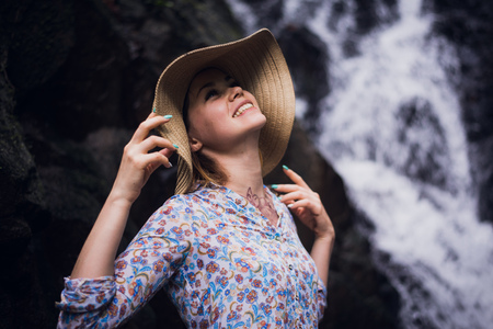Cute woman with a hat posing by the forest waterfalls