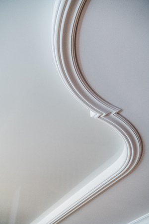 Curved decorative clay stucco relief molding on white ceiling in abstract classical style interior Stock fotó