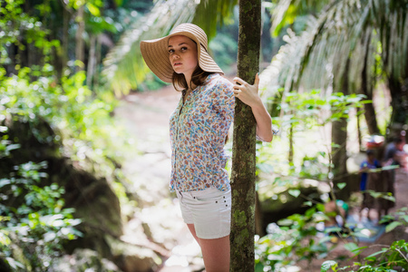 happy young woman in straw hat looking up in forest 写真素材