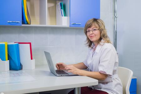 Porträt des medizinischen Experten bei der Arbeit, Kamera betrachtend, lächelnd