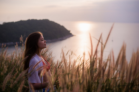 Woman in a wheat field on a summer sunset in white Stock Photo