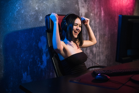 Happy cheerful cute sexy gamer girl hand gesture of win and pure emotion. Sitting at home playing video games alone on a pc computer Standard-Bild