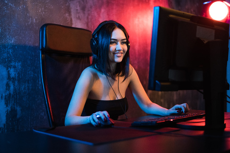 A cute female gamer girl sits in a cozy room behind a computer and plays games. Woman live streaming computer video games to her fans. Streamer and gamer concept Imagens - 104368106