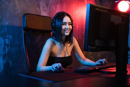 Een schattig vrouwelijk gamermeisje zit in een gezellige kamer achter een computer en speelt spelletjes. Vrouw live streaming computervideospellen naar haar fans. Streamer en gamer concept
