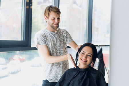 Male hairdresser smiling and talking with a customer while making a new haircut to beutiful young brunette woman Banque d'images