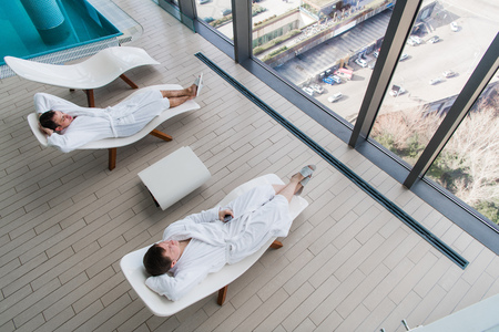 Two young man wearing bathrobe, lying on lounger in spa salon and talking to each other in front of a big window with a great city view. Spa concept