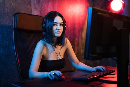 Mooie professionele gamer meisje spelen in first-person shooter online videogame op haar personal computer. Casual Cute Geek bril en glimlachen. Internetkampioenschap Cyber e-Sport. Stockfoto