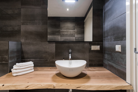 Modern interior of the bathroom. The washbasin is made of white massive shell on the table of wood. Minimalism and simplicity in a bright grey functional interior. Top view Stok Fotoğraf