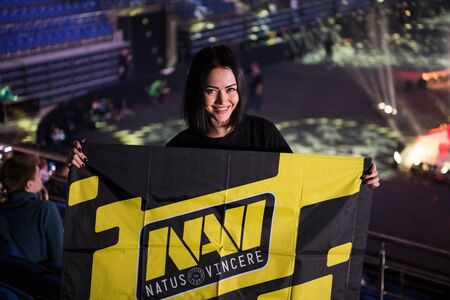 MOSCOW, RUSSIA - OCTOBER 27 2018: EPICENTER Counter Strike: Global Offensive esports event. Happy girl fan on a tribune at arena with team Natus Vincere flag. Editoriali