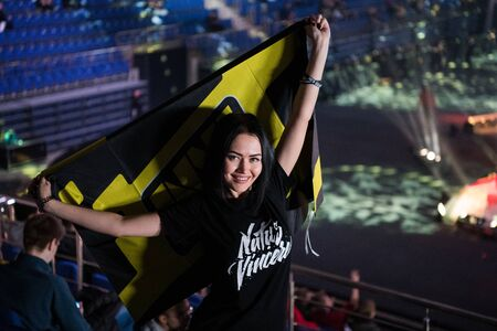 MOSCOW, RUSSIA - OCTOBER 27 2018: EPICENTER Counter Strike: Global Offensive esports event. Happy girl fan on a tribune at arena with team Natus Vincere flag.