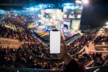 Manos de mujer con aplicación digital en el teléfono inteligente móvil en el evento de esport en big arena Foto de archivo