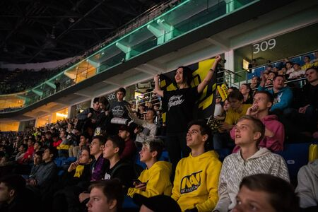 MOSCOW, RUSSIA - OCTOBER 27 2018: EPICENTER Counter Strike: Global Offensive esports event. Happy girl fan on a tribune at arena with team Natus Vincere flag. Cheering for her favorite team.
