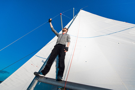 Young seaman on a sailboat standing on a sail boom. Captain of the yacht in the open sea.