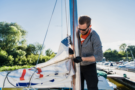 Young sailor in sunglasses holds and moves main sail with both hands. He is happy and smiling. Young man is preparing yacht for sailing. It is sunny outside.