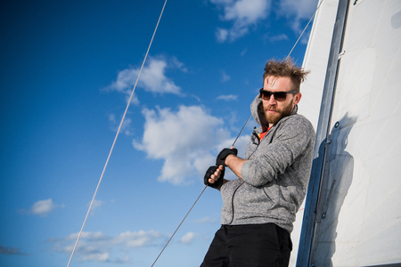 Handsome bearded sailor working with ropes on deck of a yacht against clear blue sky and sea