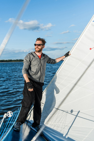 Young european man standing at edge of yacht looking at sea. Travelling on old boat with sail. Luxury lifestyle.