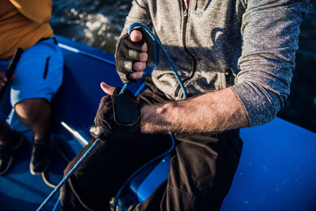 Man and woman hands ulling winch rope on sailing boat