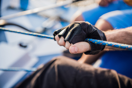 Close up of sailor winds aroung rope by using handle for coiling. He works with both hands. Young man stands on yacht. He is strong Stok Fotoğraf