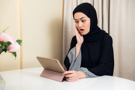 Arabian lady with hijab shocked while using a tablet computer Stock Photo