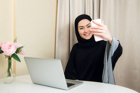Beautiful young arabic woman taking selfie with her mobile phone