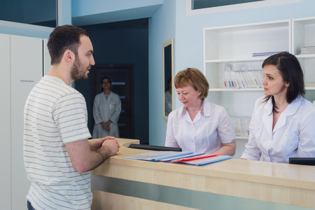 Qualified smiling doctors working with client at reception desk in hospital