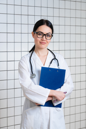 Young beautiful female doctor in white surgical coat with black stethoscope and blue paper holder in hands standing at medical office