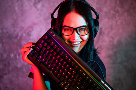 Portrait of the Beautiful Young Pro Gamer Girl standing with a gaming keyboard and headset and Looks into Camera. Attractive Geek Girl Player Wearing Glasses in the Room Lit by Neon Lights.