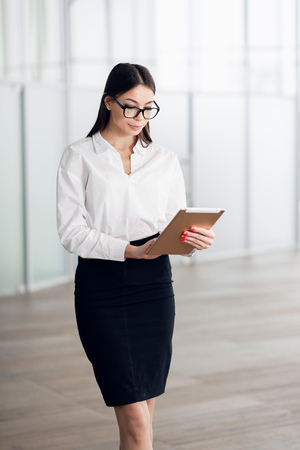 Attractive young woman wearing glasses and reading her touchscreen tablet while standing inside commercial building