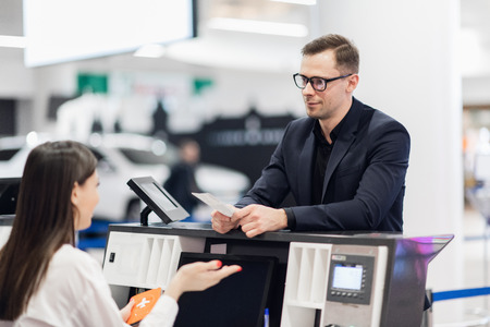 Handsome businessman handing over air ticket at airline check in counter Reklamní fotografie