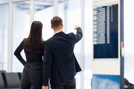 Young couple in international airport looking at the flight information board, checking her flight