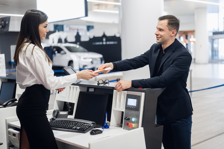 Staff At Airport Check In Desk Handing Ticket To Businessman Reklamní fotografie