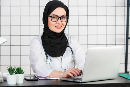 Female veiled scientist sitting on her desk with fingers on a keyboard of her laptop, smiling