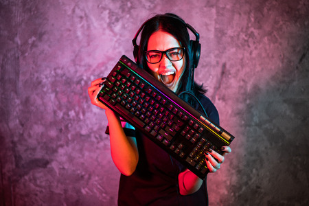 Professional Girl Gamer in MMORPG Strategy Video Game. Shes She posing over colorful blue and pink background with a gaming keyboard. She Wears Gaming Headset.